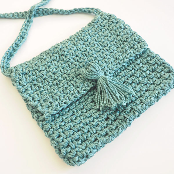 The Cute Cross Body Bag is the perfect size for all the essentials, and it's far more convenient to carry than larger totes and bags. #crochetbag #crochetpattern #crochetlove #crochetaddict