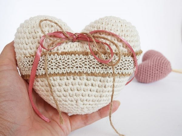 Crochet Heart Ring Pillow - Start making these cuddly crochet pillows, and you'll have all the hearts you can give when the day of love arrives! #crochetpillows #crochetpatterns #valentinecrochetpillows