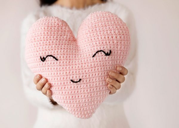 Heart Shaped Pillow - Start making these cuddly crochet pillows, and you'll have all the hearts you can give when the day of love arrives! #crochetpillows #crochetpatterns #valentinecrochetpillows