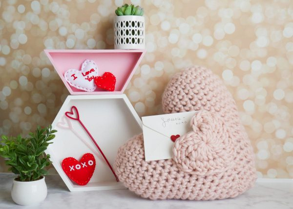 Love Note Crochet Pocket Pillow - Start making these cuddly crochet pillows, and you'll have all the hearts you can give when the day of love arrives! #crochetpillows #crochetpatterns #valentinecrochetpillows