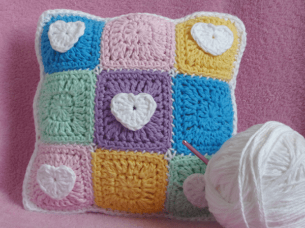 Pastel Hearts Mini Pillow - Start making these cuddly crochet pillows, and you'll have all the hearts you can give when the day of love arrives! #crochetpillows #crochetpatterns #valentinecrochetpillows